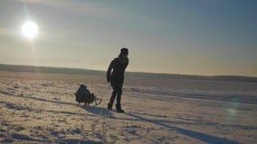 享受雪橇乘驾的小男孩 母亲雪撬他逗人喜爱的孩子 家庭户外冬天活动 有愉快的家庭 影视素材