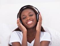享受音乐的妇女通过耳机在床上 免版税库存图片