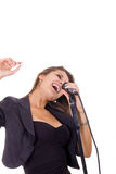 享受音乐的美丽的妇女唱歌在话筒 库存照片