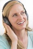 享受音乐的美丽的妇女通过耳机 图库摄影