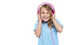 享受音乐的兴奋女孩通过耳机 免版税库存图片