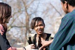 享受饮料的不同的朋友在公园 库存图片