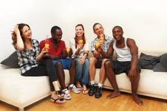 享受饮料的小组不同种族的朋友 免版税库存图片