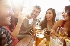 享受饮料的小组朋友在室外屋顶酒吧 库存照片