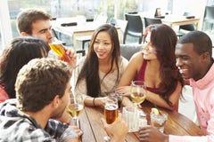享受饮料的小组朋友在室外屋顶酒吧 免版税库存照片