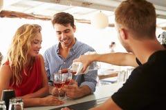 享受饮料的年轻夫妇在室外酒吧 免版税库存图片