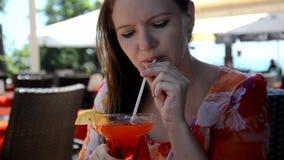 享受饮料,俏丽的在咖啡店大阳台的女孩啜饮的香蕉汁的美丽的少妇画象  影视素材