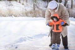 享受滑冰在户外滑冰场的家庭在一个多雪的公园在寒假期间 库存照片