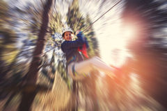 享受活动的愉快的学校女孩在一个上升的冒险公园 库存照片