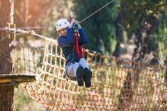 享受活动的愉快的学校女孩在一个上升的冒险公园 库存图片