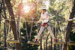 享受活动的愉快的学校女孩在一个上升的冒险公园 免版税图库摄影