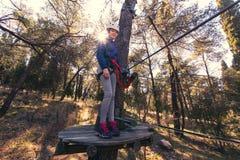 享受活动的愉快的学校女孩在一个上升的冒险公园 免版税库存图片