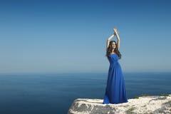 享受 塑造有礼服的愉快的美丽的妇女在蓝色sk 库存照片
