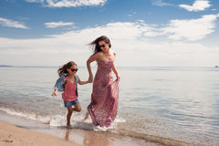 享受晴天的愉快的家庭在海滩 母亲和女儿 图库摄影