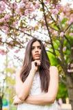 享受晴天的美丽的少妇画象在公园在樱花季节期间在一个好春日 免版税库存照片