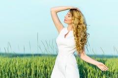 享受晴天自然的一块麦田的女孩 免版税库存图片