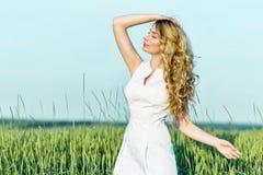 享受晴天自然的一块麦田的女孩 免版税库存照片