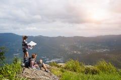 享受从山的上面的年轻背包徒步旅行者一个谷视图 免版税图库摄影