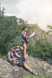 享受从山的上面的年轻背包徒步旅行者一个谷视图 免版税库存图片