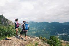 享受从山的上面的年轻背包徒步旅行者一个谷视图 库存图片