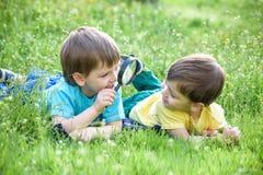 享受晴朗的晚夏和秋天天本质上在绿草的愉快的孩子 免版税库存照片