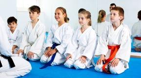 享受他们的与教练的孩子训练在空手道 免版税库存图片