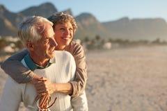 享受他们的假期的资深夫妇在海滩 库存图片