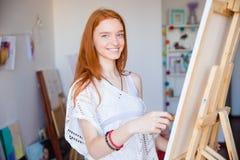 享受画的可爱的逗人喜爱的快乐的妇女艺术家在艺术车间 免版税库存照片