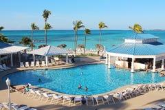 享受他们的在一种豪华旅馆手段的游泳池的几个家庭假日时间被安置接近一个加勒比海滩 库存照片