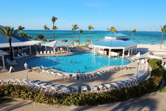 享受他们的在一种豪华旅馆手段的游泳池的几个家庭假日时间被安置接近一个加勒比海滩 免版税库存照片