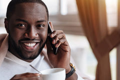 享受他的在咖啡馆的微笑的非裔美国人的人晚餐 免版税库存图片