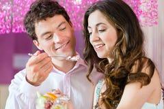 享受他们的时间的年轻夫妇在冰淇凌店里 库存图片