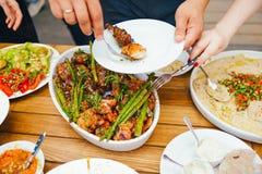 享受Dinning吃概念的朋友幸福 食物自助餐 承办的用餐 吃党 共享概念 免版税库存图片