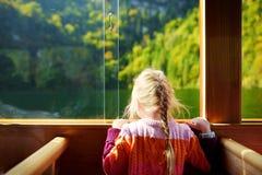 享受Konigssee深绿水的看法小女孩,当旅行乘电小船时 免版税库存图片