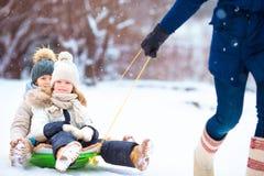 享受sledding的小女孩 父亲sledding他的小可爱的女儿 自户外圣诞前夕的家庭度假 库存图片