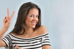 享有与和平gestu的可爱的逗人喜爱的愉快的少妇生活 免版税库存图片