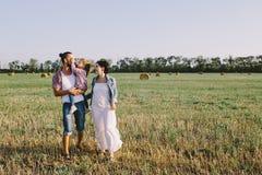 享有生活的父亲、女儿和怀孕的母亲室外在领域 免版税图库摄影