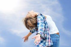 享有生活的自由的女孩 微笑反对天空的美丽的妇女 免版税库存照片