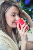 享用一个大杯子新近地酿造的热的茶的妇女,她在一个沙发放松在客厅 穿戴女孩褂子早晨白色的咖啡杯 免版税库存照片