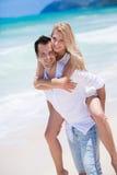 享用一个孤零零海滩的愉快的年轻夫妇backriding 库存图片
