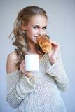 享用一个新鲜的酥脆新月形面包的妇女 库存图片