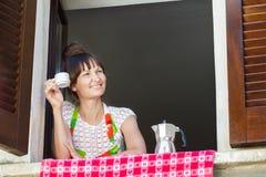 享用一个杯子与坐在开窗口附近的意大利moka罐的新近地煮的咖啡的少妇画象与 库存图片