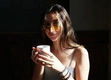 享用一个杯子热的咖啡的美丽的青少年的女孩 免版税库存图片