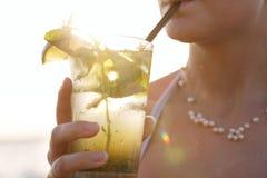 享用一个热带mojito鸡尾酒的妇女 免版税库存照片