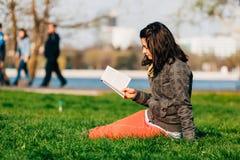 享用一本好书在公园 库存照片