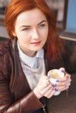 享用一杯咖啡在咖啡馆的年轻可爱的妇女 库存照片