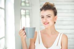 享用一杯咖啡或茶的美丽的年轻欧洲妇女,当放松在明亮的绝尘室时 免版税库存图片