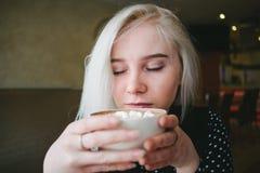 享用一杯咖啡用在咖啡馆的蛋白软糖一个年轻美丽的白肤金发的女孩的画象 免版税图库摄影