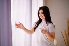 享用一杯咖啡的妇女在清早 免版税库存图片