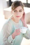 享用一杯咖啡的美丽的妇女户外 免版税图库摄影